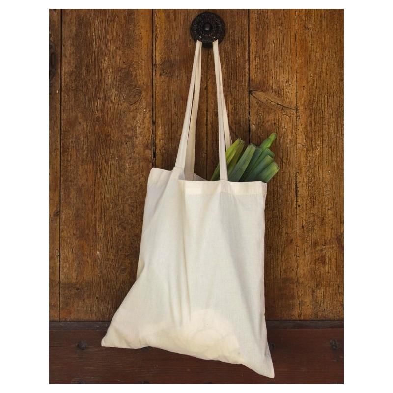Bolsa tote bag orgánica de color beige o natural colgada de las asas fondo madera